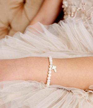 lauren hinkley pearl cross bracelet. on arm